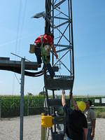 A Tower Tech employee has attached the 10 watt solar panel to the tower and is about to install the 900 MHz yagi antenna